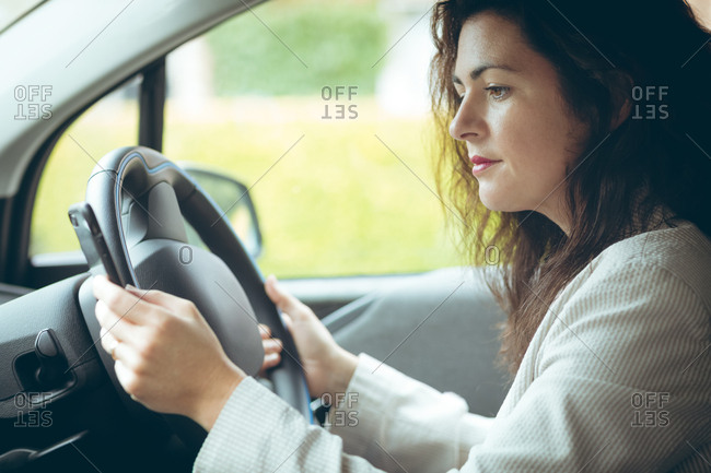 Beautiful businesswoman using mobile phone while driving car