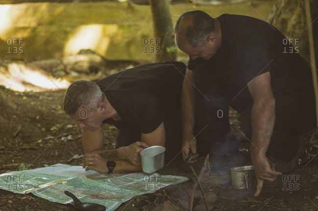 Two fit men looking at map in boot camp