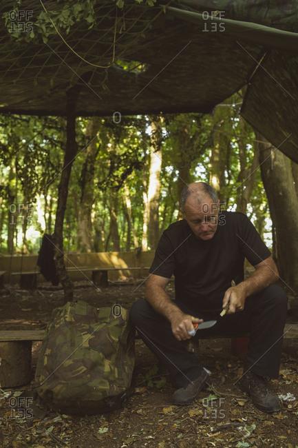 Mature man sharpening stick at boot camp