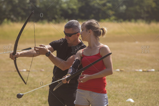 Trainer instructing woman about archery at boot camp