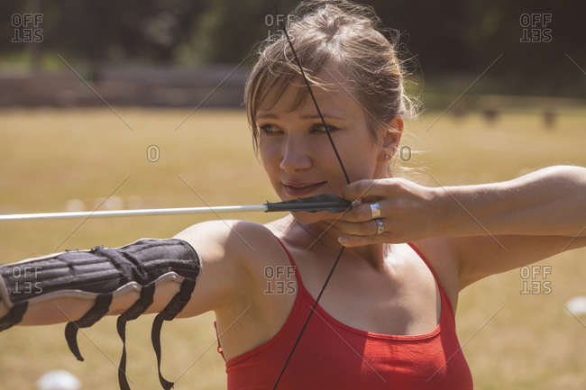 Woman practicing archery at boot camp on a sunny day