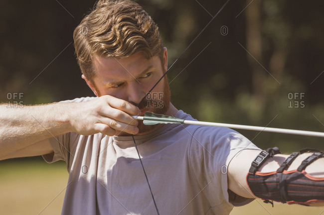 Man practicing archery at boot camp on a sunny day