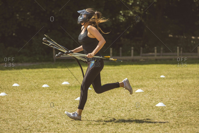 Woman running while training in boot camp on a sunny day