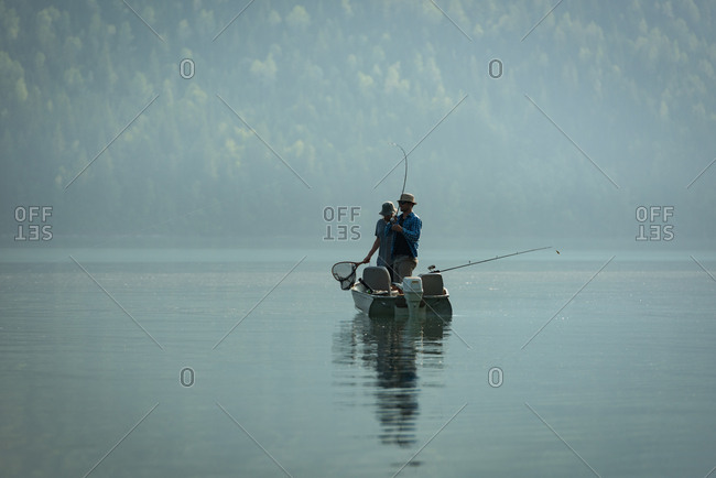 Two fishermen fishing in the river on a sunny day