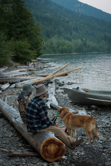 Two fishermen fishing near riverside at countryside