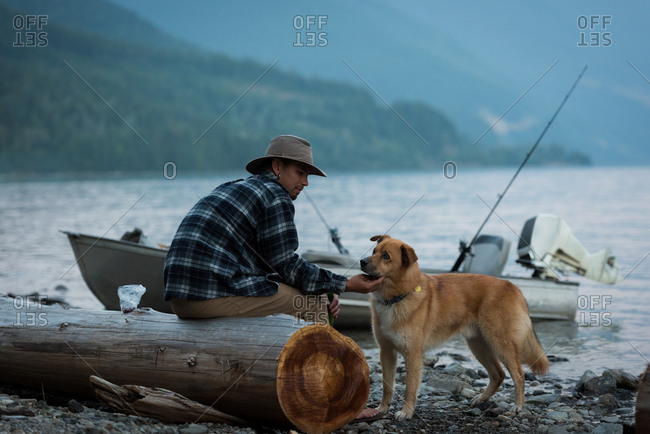 Fisherman petting his dog near riverside at countryside