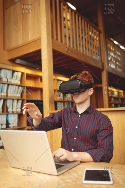 College student using laptop and virtual reality headset in library