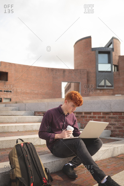College student using laptop on stairs in college