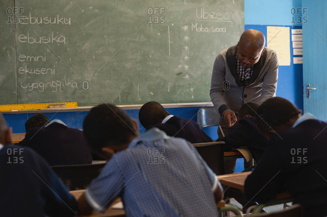 Male teacher teaching students in the class at school