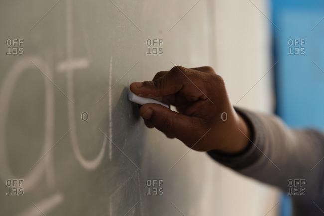 Male teacher explaining on chalkboard in classroom