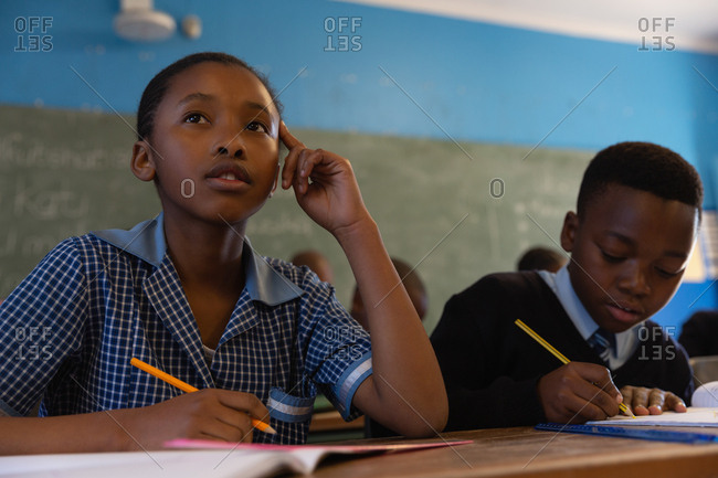 School kids holding sketch pens in classroom at school