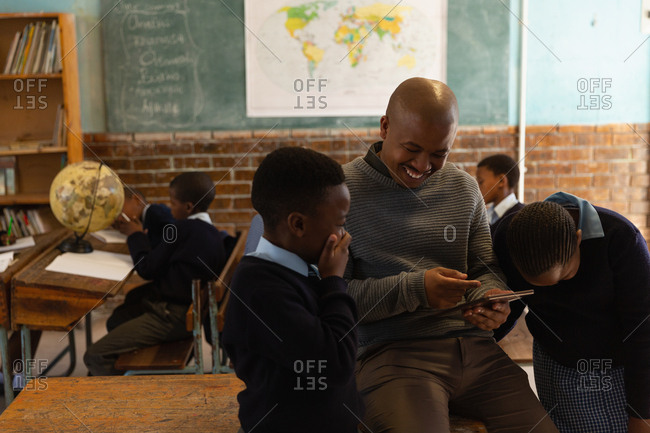 Male teacher using digital tablet with students in classroom at school
