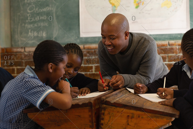 Male teacher teaching students in the classroom at school