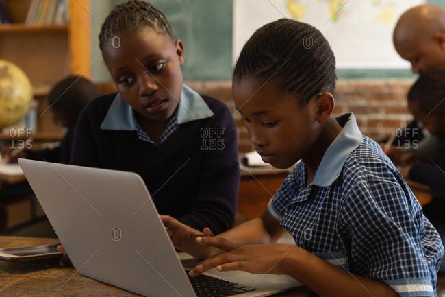 School kids using laptop in classroom at school