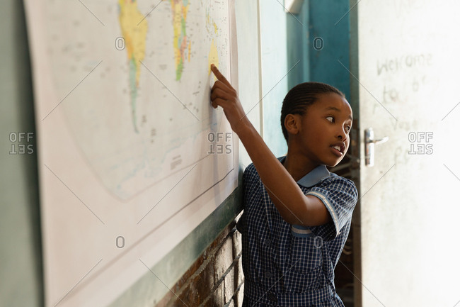 Schoolboy explaining about world map in classroom at school