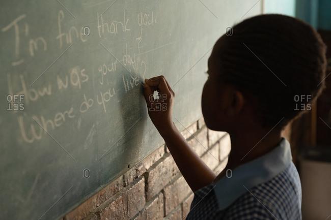 Schoolgirl writing on chalkboard in classroom at school