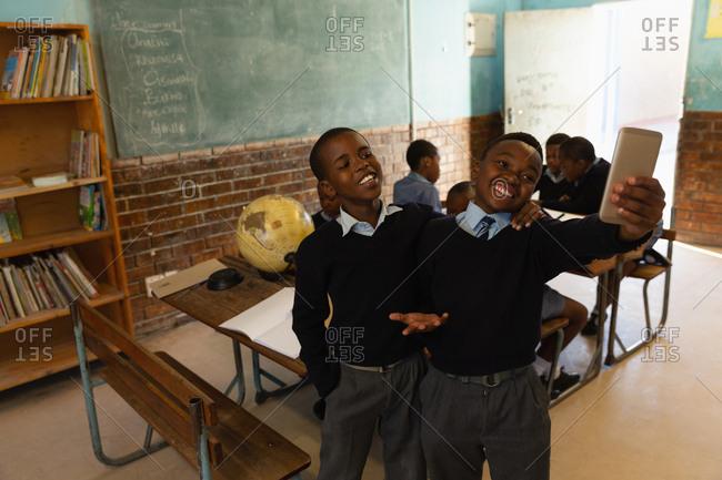 School kids taking selfie with mobile phone in classroom at school