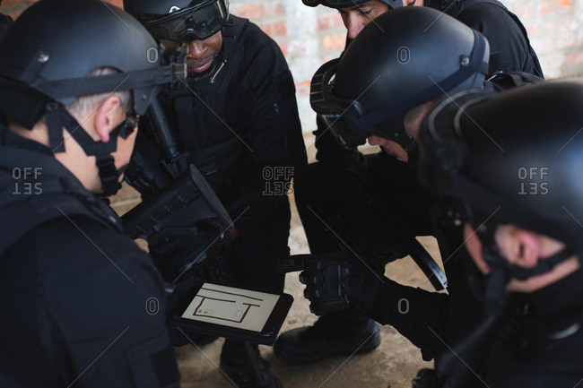 Military soldiers discussing their plan over digital tablet during military training