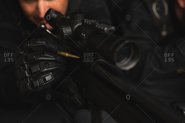 Close-up of military soldier using gun machine in training