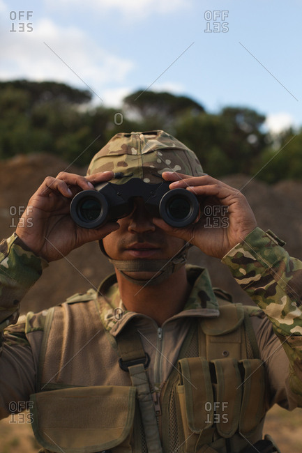 Military soldier looking through binoculars during military training