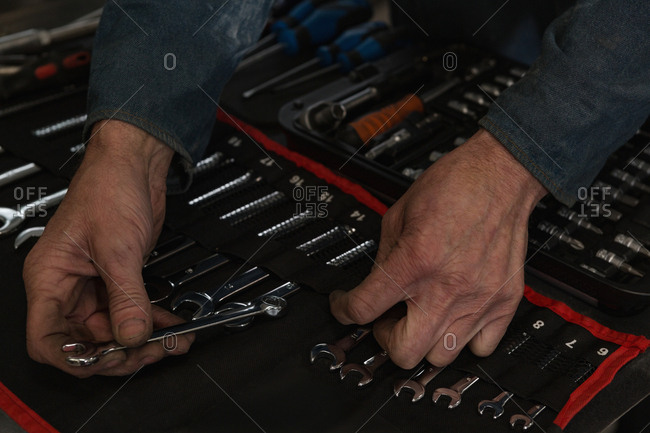 Close-up of mechanic arranging tools in garage