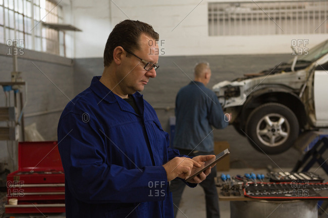Side view of male mechanic using digital tablet in garage