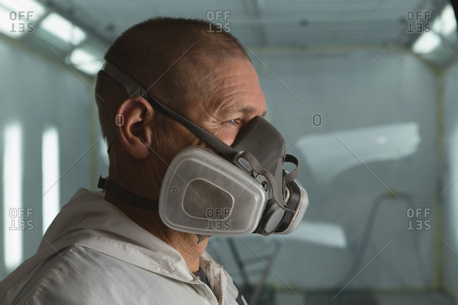 Close-up of mechanic with gas mask in garage