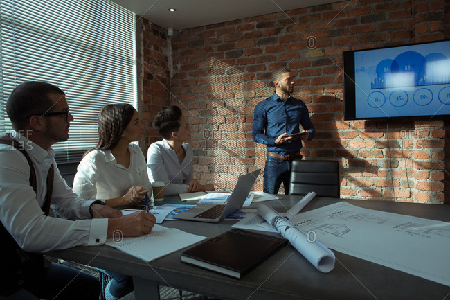 Executives giving presentation on screen in office