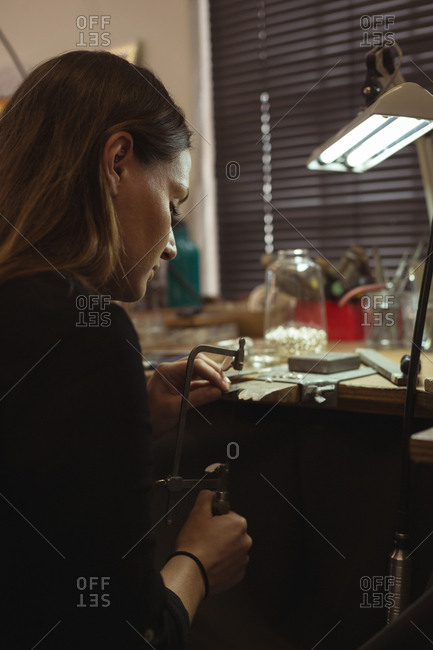 Attentive jewelry designer making jewelry in workshop