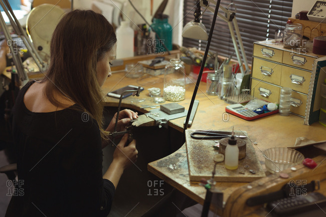 High angle view of jewelry designer making jewelry in workshop