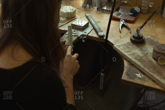 Rear view of jewelry designer making jewelry in workshop