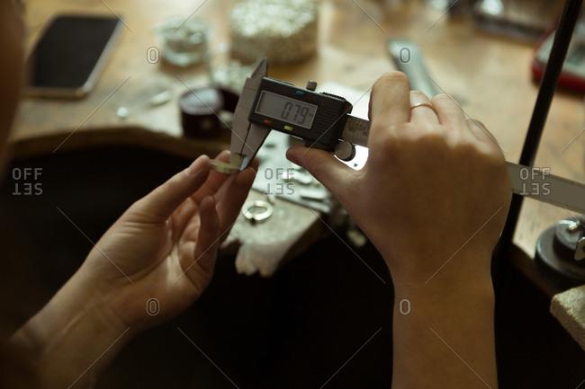 Close-up of jewelry designer using caliper in workshop