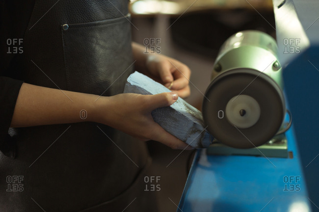 Close-up of jewelry designer using sharpening machine