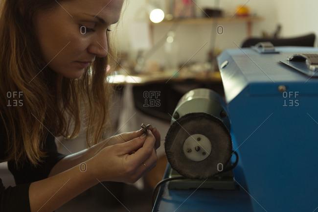 Jewelry designer using sharpening machine in workshop