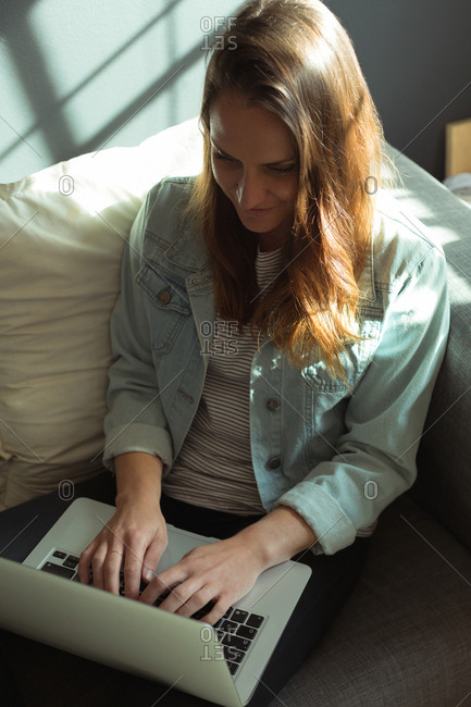Female jewelry designer using laptop at home
