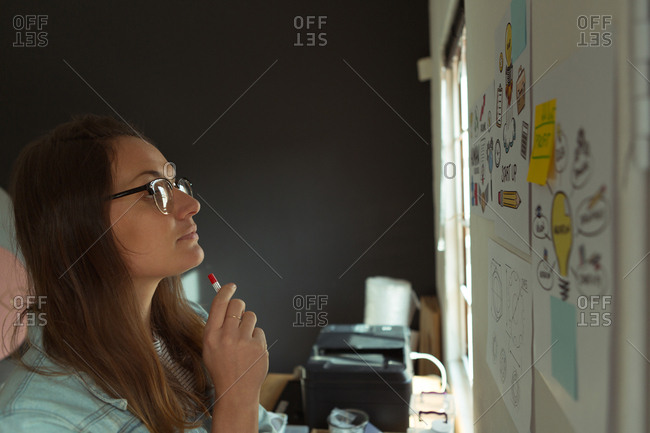 Thoughtful jewelry designer looking at chart in home