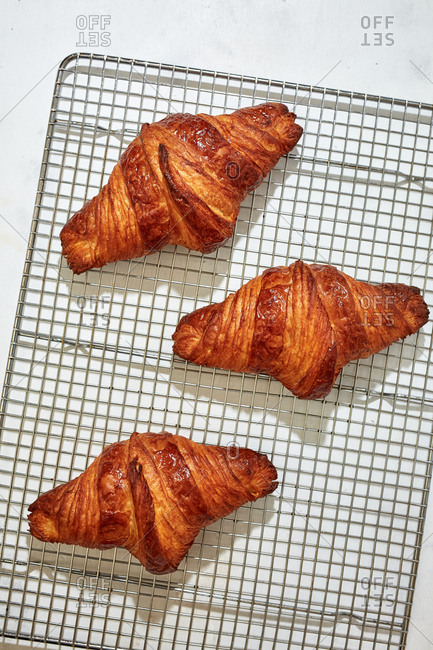 Freshly baked croissants on cooling rack