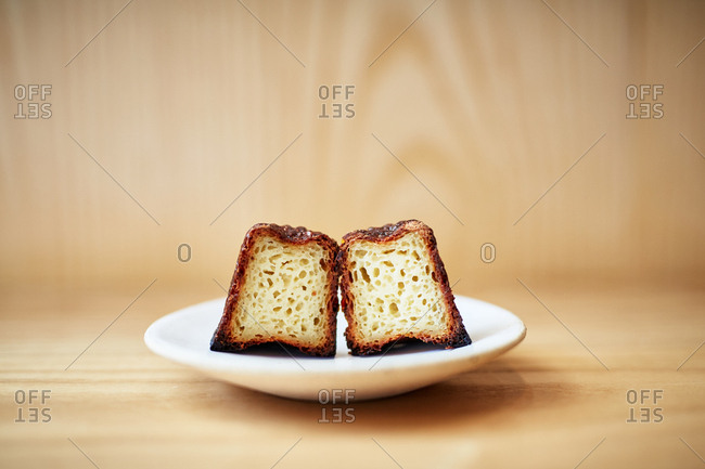 Freshly baked canele cut in half and served on a plate
