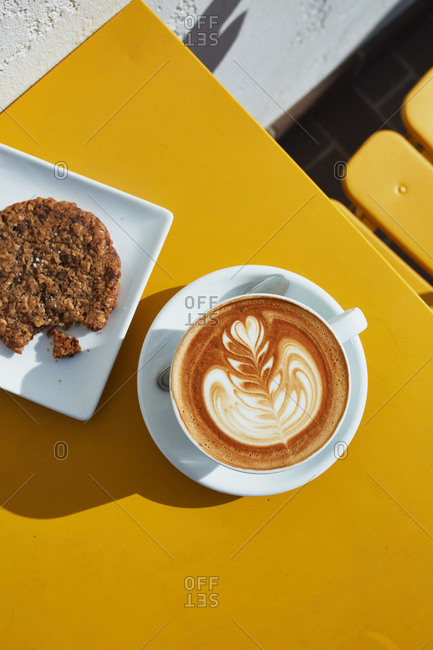 Freshly brewed latte served with cookie