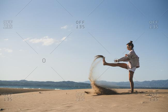 Teenage girl throwing sand on the beach