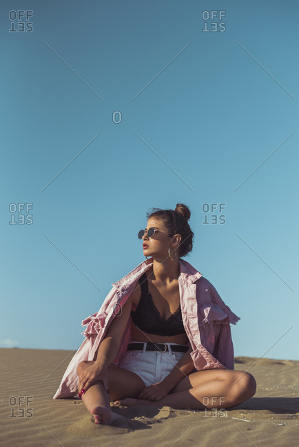 Teenage girl sitting on beach dune against blue sky
