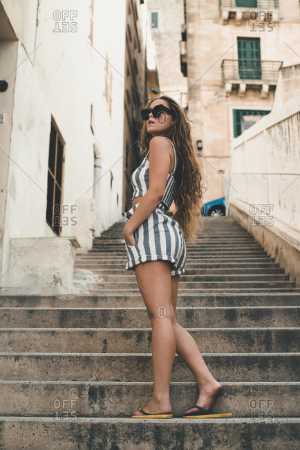 Teenage girl wearing striped beach wear, posing on stairs