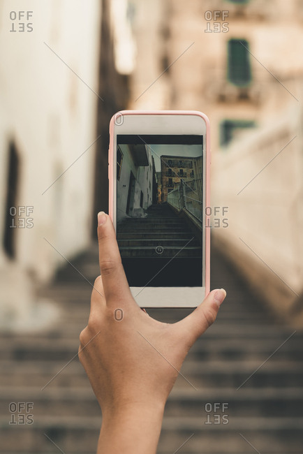 Malta, Valletta, Hand of woman taking cell phone picture of a street