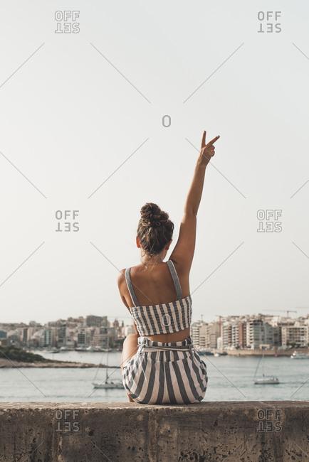 Teenage girl wearing striped beach wear, sitting on wall with raised arm
