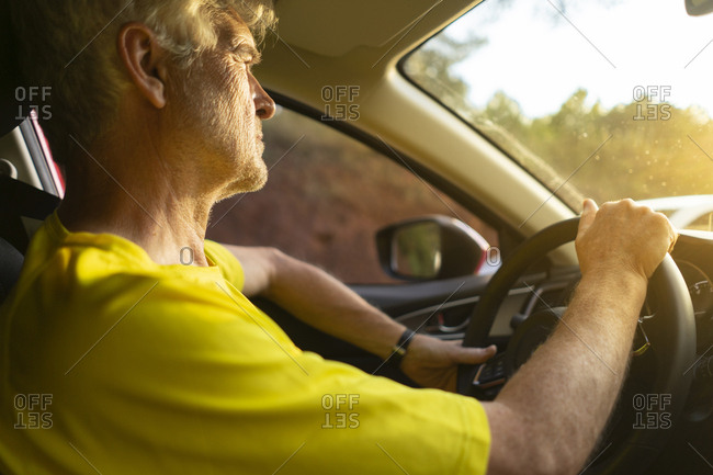 Senior man driving a car during sunset