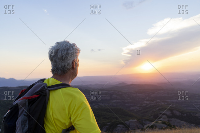 Spain, Catalonia, Montcau, senior man looking at view from top of hill during sunset