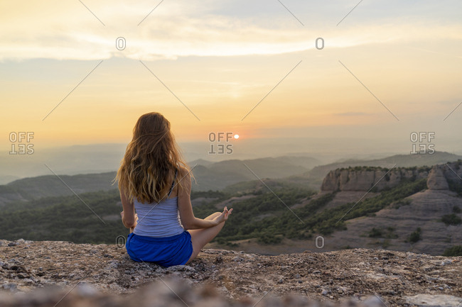 Spain, Catalonia, Sant Llorenc del Munt i l'Obac, Woman meditating in the mountains