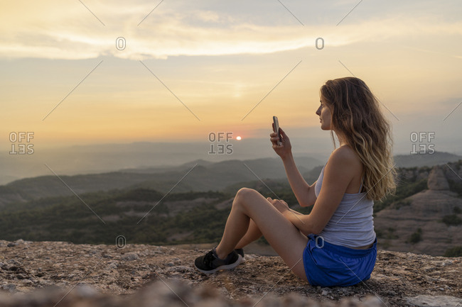 Spain, Catalonia, Sant Llorenc del Munt i l'Obac, woman taking pictures in the mountains with her smartphone