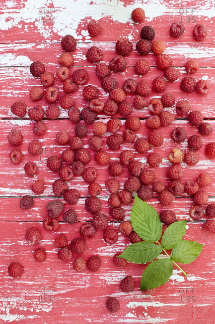 Raspberries and leaf on wood