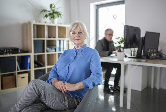Senior businesswoman sitting in office with colleague working behind her